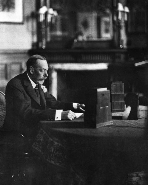 King George V (1865 - 1936), seated at the microphone in a room at Sandringham from where he broadcast a Christmas message to the British Empire. Date: 1934