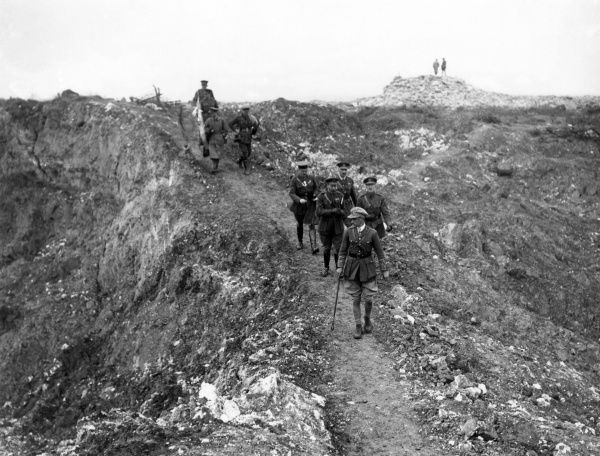 King George V passing between two mine craters near Mametz in The Somme, northern France, in a party guided by Mr Harding of the Royal Engineers