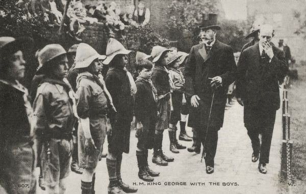 King George V inspecting a line of boy scouts, who are standing to attention. A group of people are watching from the top of a wall. The man accompanying the King is smoking, which doesn't seem very respectful. Date: early 20th century