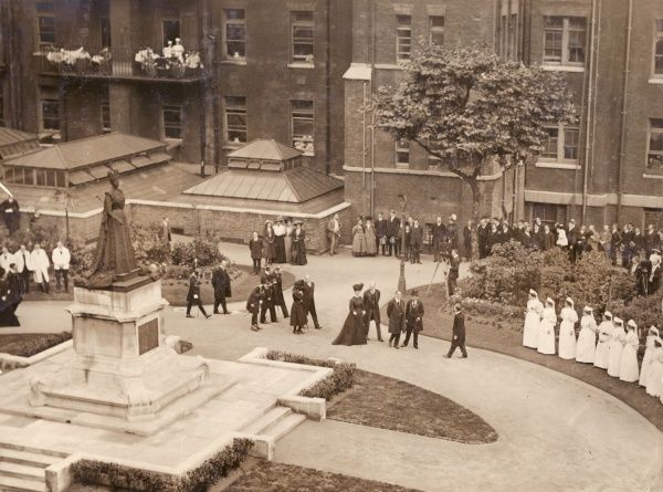 King George V and Queen Mary on a visit to the London Hospital in Whitechapel, East London. The statue is of Queen Alexandra, George V's mother -- she became President of the hospital in 1904, and her statue was erected in 1908