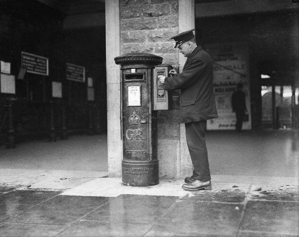 An English postman in his uniform, demonstrates the knack of buying a book of stamps from a vending machine attached to a King George V pillar box
