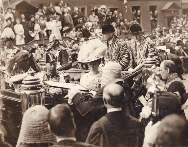 King George V receiving an Address from the Benchers (senior lawyers) at Gray's Inn, London. Queen Mary sits next to him in an open carriage