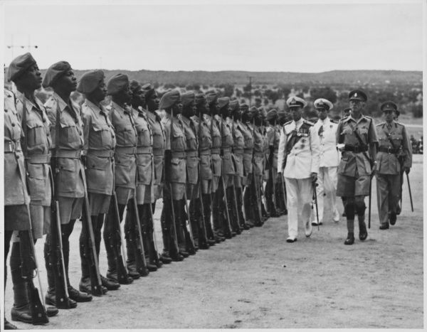 ROYAL TOUR OF SOUTH AFRICA & RHODESIA: King George VI inspects a row of African soldiers at a military parade