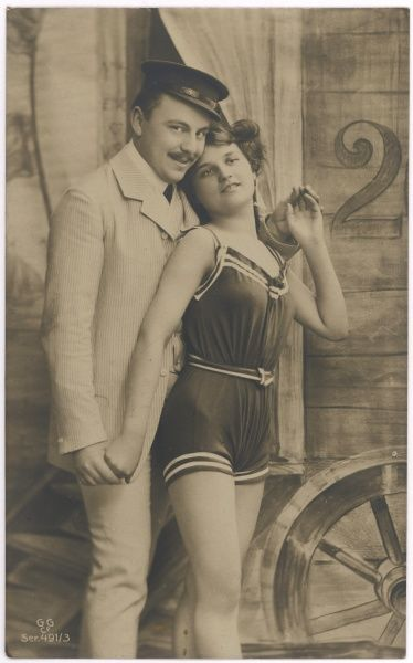 A young German lady in a one- piece bathing costume with a belt poses with a fully clothed gentleman friend outside a bathing machine