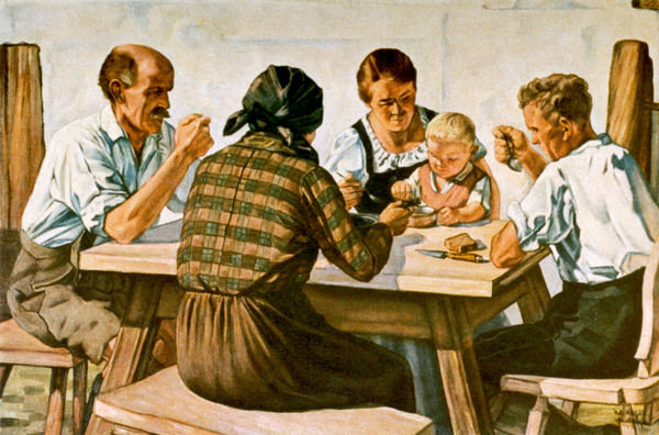 FAMILY MEAL Three generations of an idyllic German country family partake in a family meal in a farmhouse kitchen