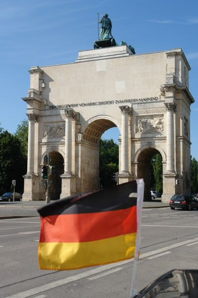View of a waving German flag in front of the triple-arched Siegestor (Victory Gate or Triumphal Arch) in Munich, Bavaria, Germany