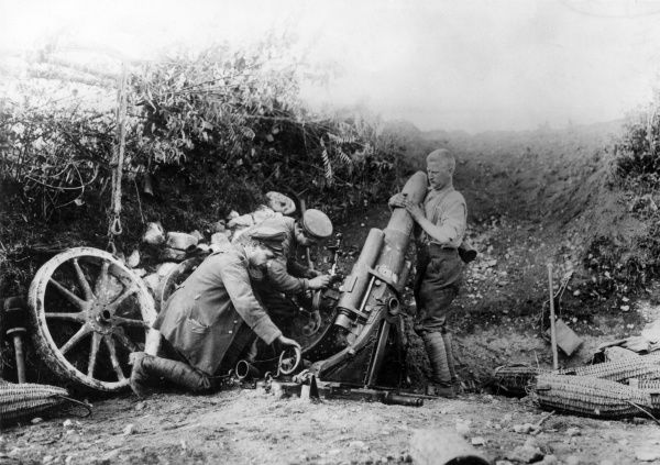 German gunners in a gun emplacement, preparing a 25cm muzzle-loading heavy trench mortar for firing during the First World War. Protective wickerwork shell containers can be seen on the ground on the right. Date: 1914-1918
