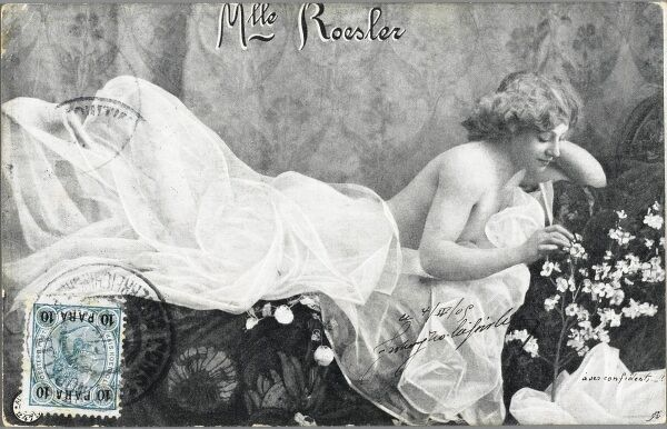 A German Music Hall entertainer, Mademoiselle Roesler, posing for a portrait photographer in an alluring position under a white sheet. She is admiring some small white flowers