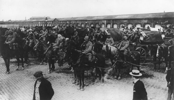 Scene during the German occupation of Brussels, Belgium, during the First World War. Showing German supply wagons outside a depot, and German troops on horseback. Date: 1914-1918