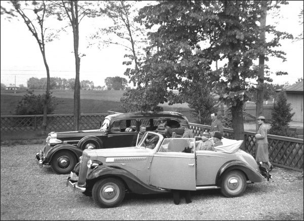 Visitors or dignitaries and German officials in two (possibly Embassy) vehicles. Both cars are American Packards. Photograph by Ralph Ponsonby Watts