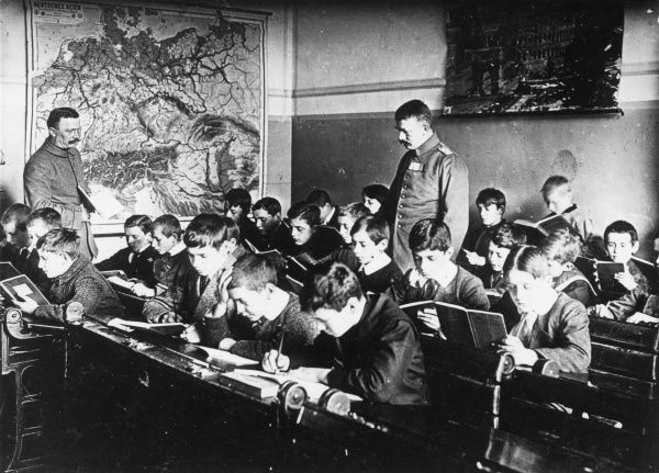 A German-run school in Brussels, Belgium, during the First World War. Showing boys at their desks with two teachers in uniform. Date: 1914-1918