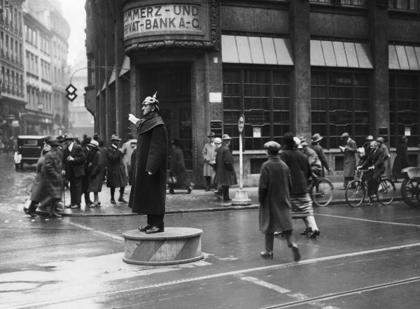 A German traffic policeman in a helmet with a spike on it standing on a podium in the middle of the road. Date: 1930s