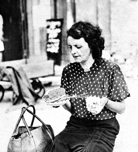 Photograph showing a German woman in Berlin holding her daily ration: a small piece of bread, a few carrots and some dehydrated potatoes, August 1945