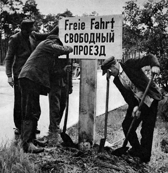 Photograph showing German workers re-erecting a Russian and German sign declaring 'Free Passage' on the border between West Berlin and the Soviet Sector at the end of the Berlin Blockade, May 1949. Between April 1948 and May 1949 Josef Stalin