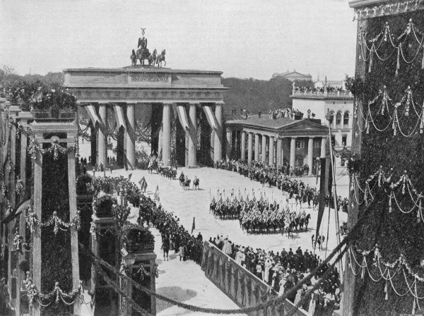 An Imperial procession passes through the Brandenburger Thor with banners waving, trumpets blaring and all the panoply of Prussian militarism