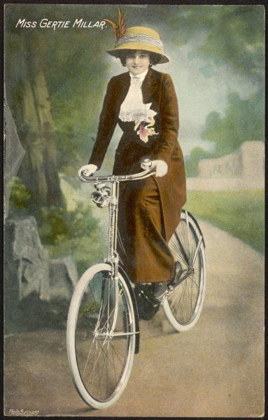 Popular actress Gertie Millar photograpjed on a bicycle in a studio setting