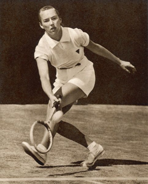 Gertrude Moran, American tennis player known as 'Gorgeous Gussie' by Wimbledon fans, due in part to the frilly pants designed by Teddy Tinling she wore in 1949. Pictured here wearing boy's shorts with a red ribbon in her hair, on Court No