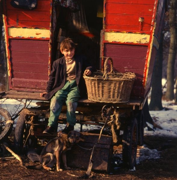 A smiling gipsy boy sitting on the back step of his red and yellow caravan, with a large basket at his side, and a pet dog at his feet