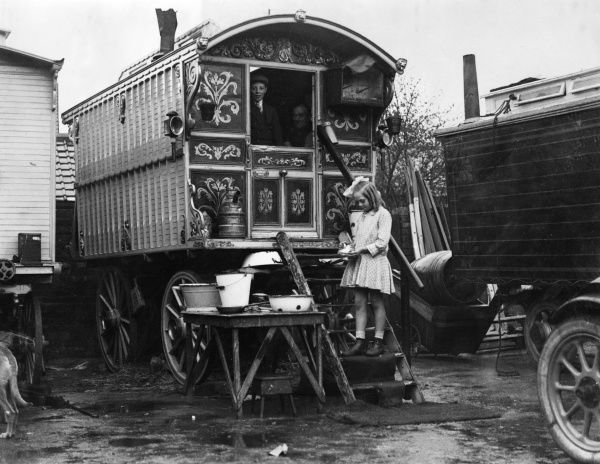 A smart little gipsy girl with ringlet stands on the steps of a gipsy caravan. An old man and a boy, perhaps her grandfather (or father) and brother are in the caravan. Date: 1920s
