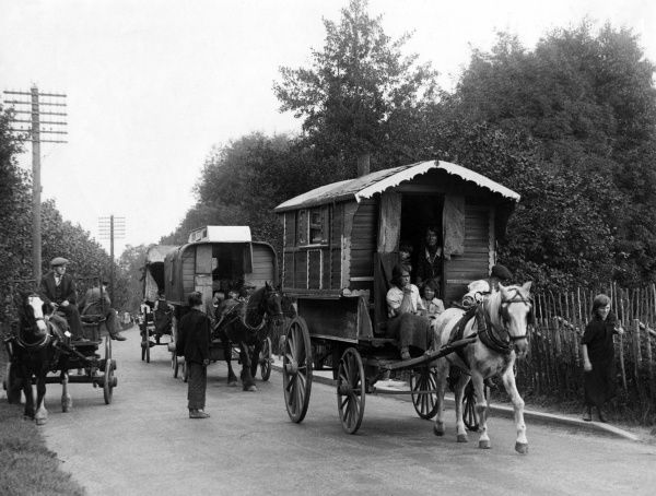 Gipsy caravans on the road, on their way to hop fields near Paddock Wood, Kent, England. Date: 1930s