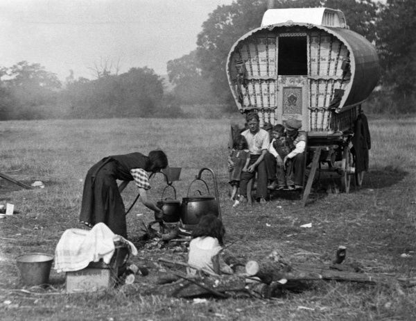 Mother gets the fire ready to cook the food in huge pots at a gipsy encampment, while the menfolk mind the children on the caravan steps, England. Date: 1930s
