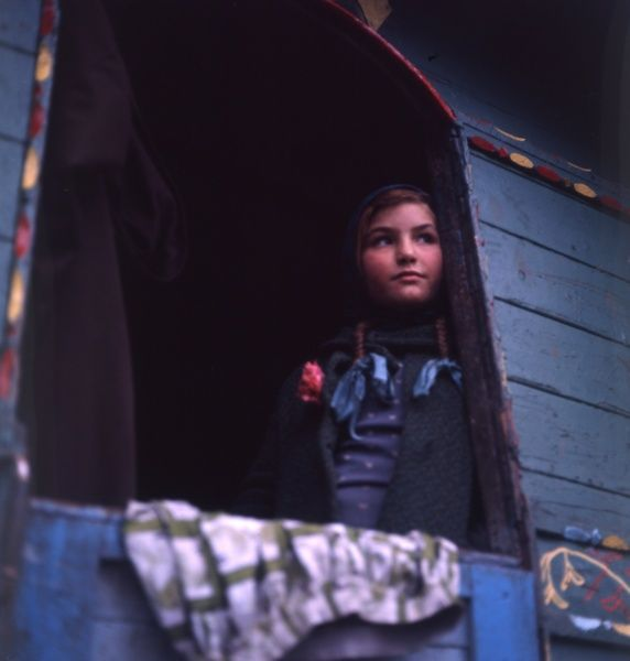A gipsy girl with plaited hair looking out of the back of her caravan