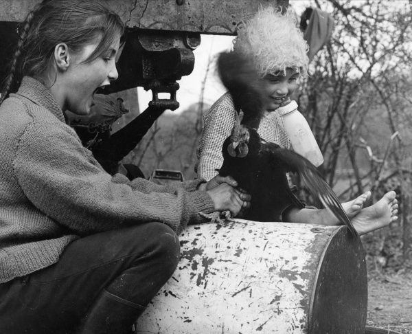 Two gipsy girls with a chicken, sitting on the ground at the side of their caravan. The older girl wears a knitted jumper and has plaited hair. The younger girl has bare feet and is holding a feeding bottle in her mouth