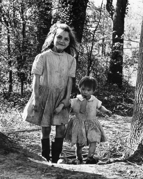 Two gipsy girls, Janie and Daphne, walking through a wood in Charlwood, Surrey. Their dresses are very dirty, and the smaller girl is holding a feeding bottle in her mouth