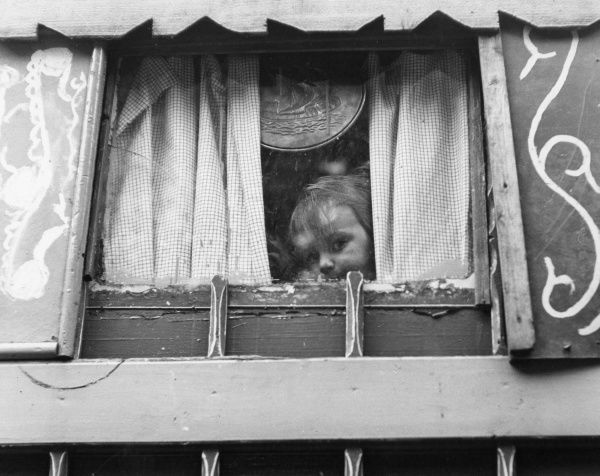 A gipsy toddler peeping out of the back of his caravan, through half-closed curtains