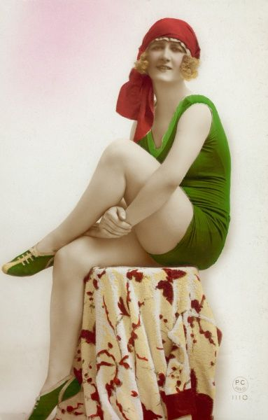Girl in green bathing costume and red head scarf poses on a small table