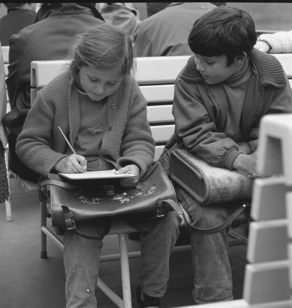 A girl and boy with their school satchels, sitting on a bench. The girl is writing something in her notebook, while the boy watches