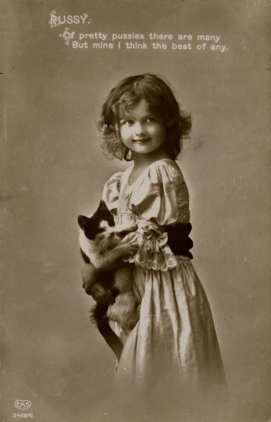 A little girl holding her favourite pussy cat. Date: 1912