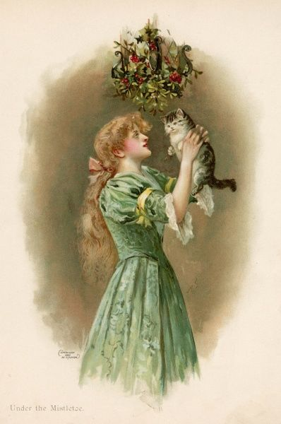 A girl holds up her cat beneath the mistletoe