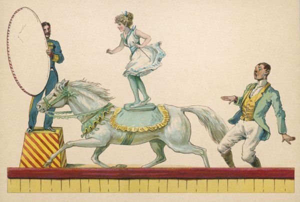 A girl standing on the back of a grey horse prepares to jump through a paper hoop