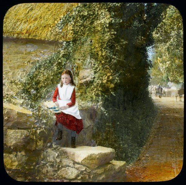 A girl sitting on a wall by a country lane on a summer's day