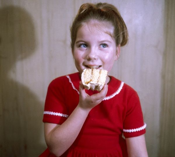 A gleeful little girl takes a bite out of a huge slice of iced cake!