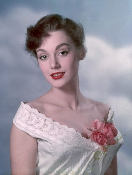 A young, doe-eyed woman, wearing a broderie anglaise camisole top & pink rose floral corsage, smiles nervously at the camera