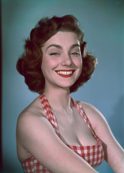 An engaging young brunette model with a broad, bright smile wears a halter-neck gingham sun-top. Date: 1950s
