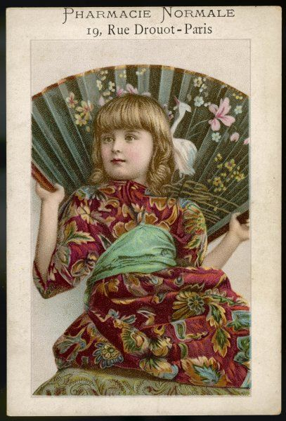 A European girl, dressed in Oriental style, holds a large fan