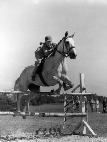 A happy girl Show Jumping with her horse over a hurdle. Date: early 1950s