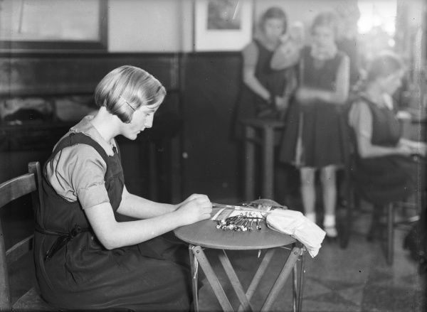 A schoolgirl learning the art of lacework at the London County Council Handicraft School