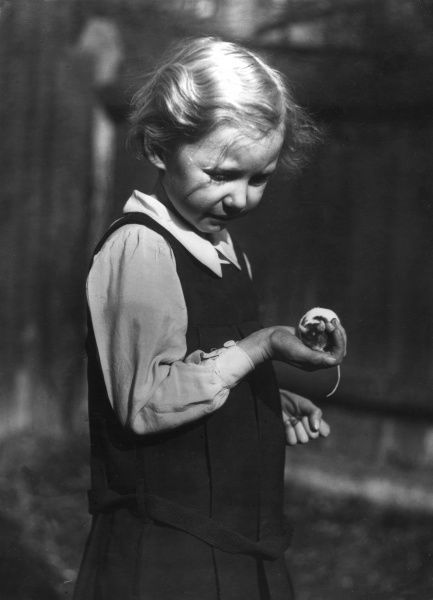A little girl holding her pet mouse in the palm of her hand. Date: 1930s