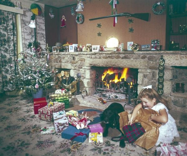 A spoilt little girl sits next to the log fire with her dog and opens present after present!