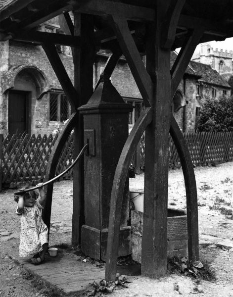 A little girl puts her weight behind the old village water pump on the village green at Lullington, Somerset, England. Note the massive oak timbers of the canopy. Date: 1950s