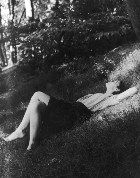 A young woman with bare feet lies on her back on a grassy bank and stares up at the sky in a mood of relaxation and contemplation