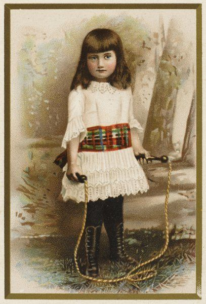 A girl in a white dress with a tartan sash with her skipping rope