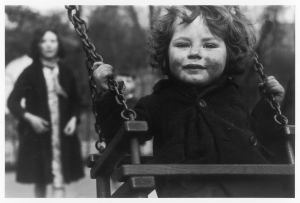 A grubby little working class girl on a swing
