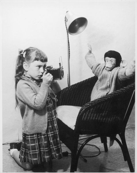 A young girl takes a photograph of her toy monkey