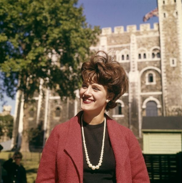 A young woman wearing a red jacket and a pearl necklace, a carefree 'girl about town' doing a spot of sightseeing near the Tower of London