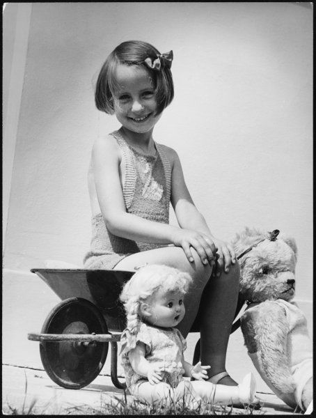 A sweet little girl in a knitted bathing costume with a ribbon in her hair, sits in a toy wheelbarrow and has her picture taken with her favourite doll and teddy bear